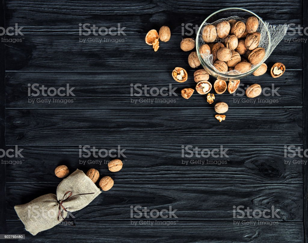 Some walnuts on a black wooden table background. stock photo