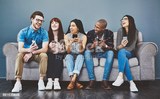 Studio shot of young people using wireless technology against a gray background
