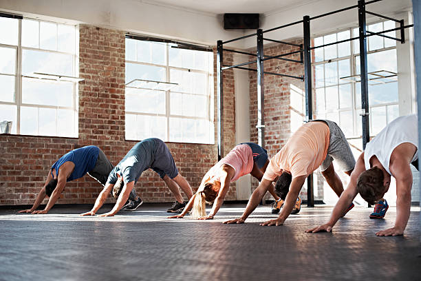 Some yoga for good measure Shot of a group of people stretching in a fitness class yoga class stock pictures, royalty-free photos & images