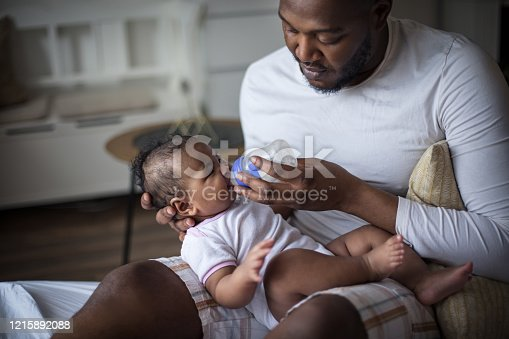 Somebody's hungry. African American father feeding his daughter.