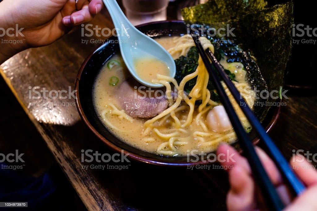 Someone eating a delicious looking bowl of tonkotsu ramen stock photo