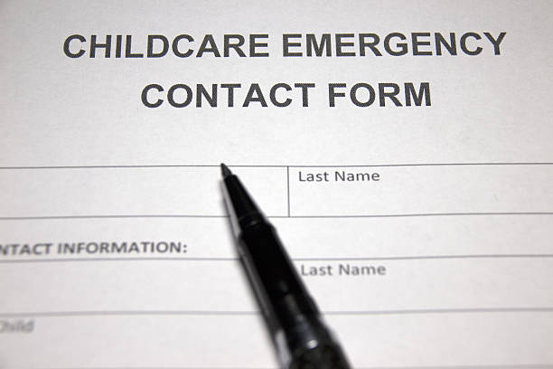 someone filling out childcare emergency contact form stock photo