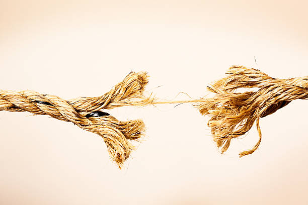 Someone has reached breaking point symbolized by snapping rope. stock photo