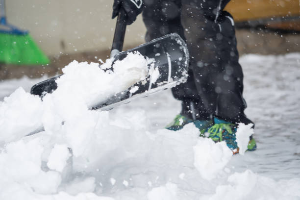 Someone is  shoveling snow outside in winter while it is snowing stock photo