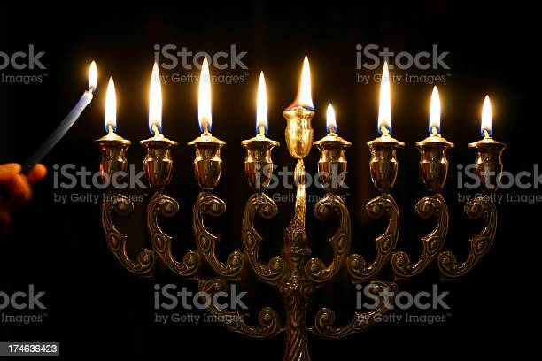 Someone Lighting The Last Candle Of A Menorah Stock Photo - Download Image Now