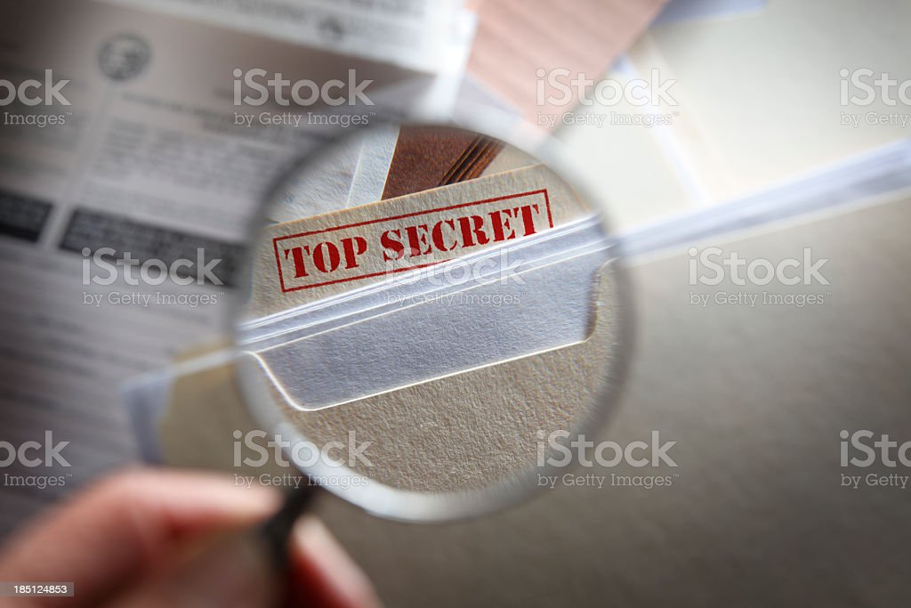Someone looking at top secret files with magnifying glass stock photo