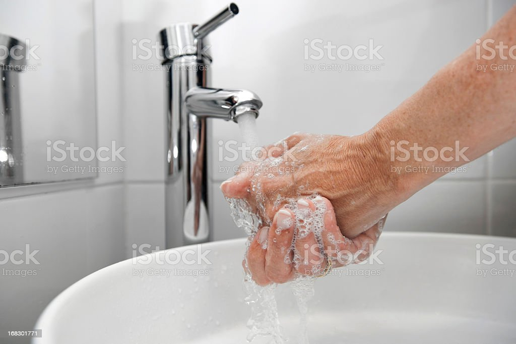 Someone washing their hands in a white sink and a silver tap stock photo