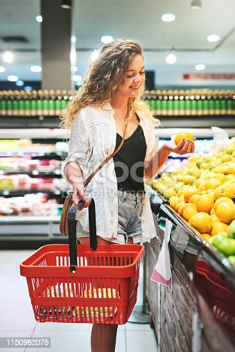 Shot of a beautiful young woman picking oranges while shopping at a grocery store