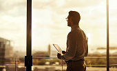 Silhouette of a mature businessman standing in front of an office window and using a digital tablet