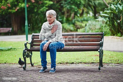 Shot of a senior woman suffering from a heart attack in the park