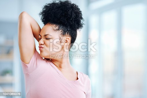 Shot of an attractive young woman smelling her armpits during her morning routine