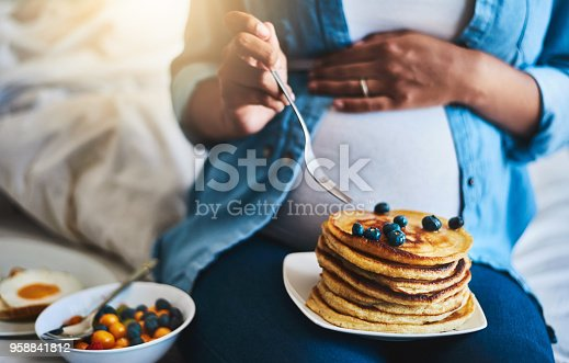 Cropped shot of a pregnant woman eating delicious pancakes at home