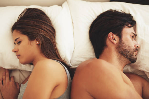 Something's gone wrong Shot of a young couple lying in bed and ignoring each other husband stock pictures, royalty-free photos & images