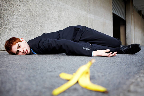 Sometimes banana skins are unavoidable A young man lying on the ground after slipping on a banana peel banana peel stock pictures, royalty-free photos & images