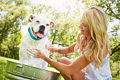 Shot of a woman bathing her pet dog outside on a summer's day
