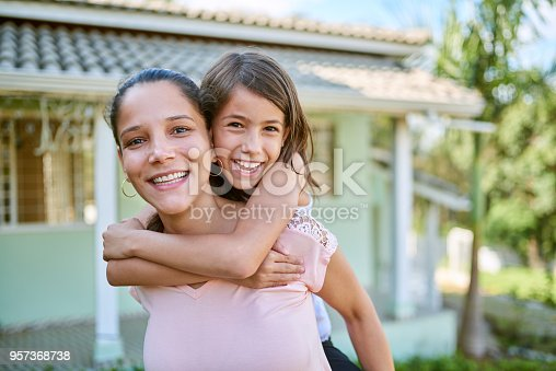 Portrait of a happy mother and daughter playing together in their backyard