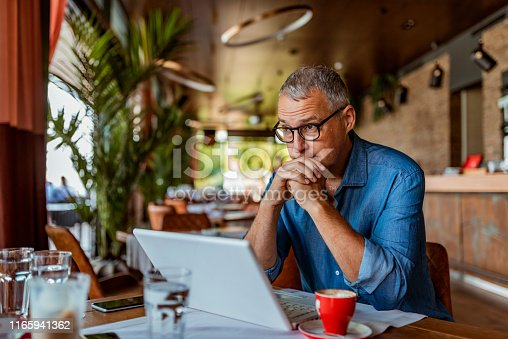 Contemplating businessman in the restaurant feeling sad. Full concentration on work. Confident mature man working on laptop while sitting at his working place in office. Tired manager sitting in restaurant surrounded with coffee and laptop computer having tired look , having pain, being sleepy and exhausted. Tiredness.