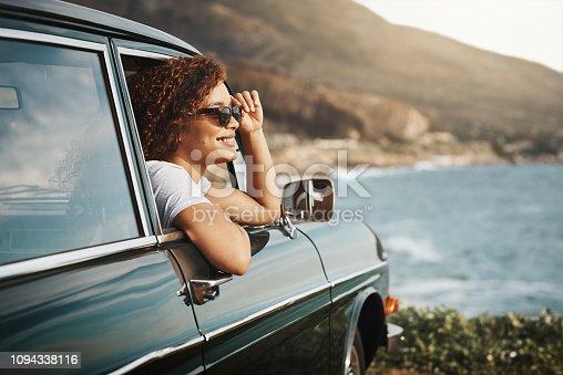 Shot of a young woman enjoying a road trip