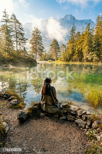 Young woman meditating while sitting, relaxing alone while looking at view, lake and mountains sunny landscape on background outdoor. Travel healthy Lifestyle concept.  Scenic surroundings near famous lake Eibsee. Wonderful day gorgeous scene. Location resort Garmisch-Partenkirchen, Bavarian alp, sightseeing Europe. Outdoor activity. Explore the world's beauty.