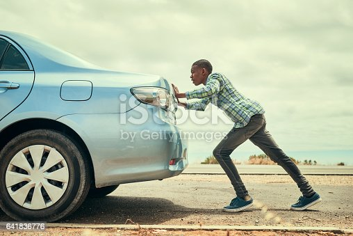 Full length shot of a young man pushing his car along the road after breaking down