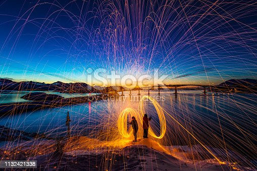 Spectacular sunset Sommaroy Island light painting sparks spinning Northern Norway Scandinavian winter landscape Europe
