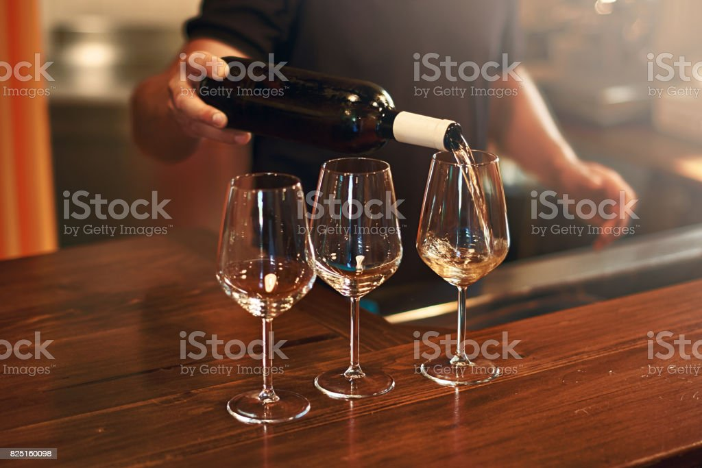 Sommelier fills the glasses during pinot gris wine tasting stock photo