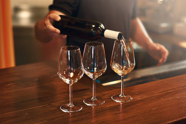 Sommelier fills the glasses during pinot gris wine tasting Sommelier pours pinot gris wine in glasses for degustation winetasting stock pictures, royalty-free photos & images