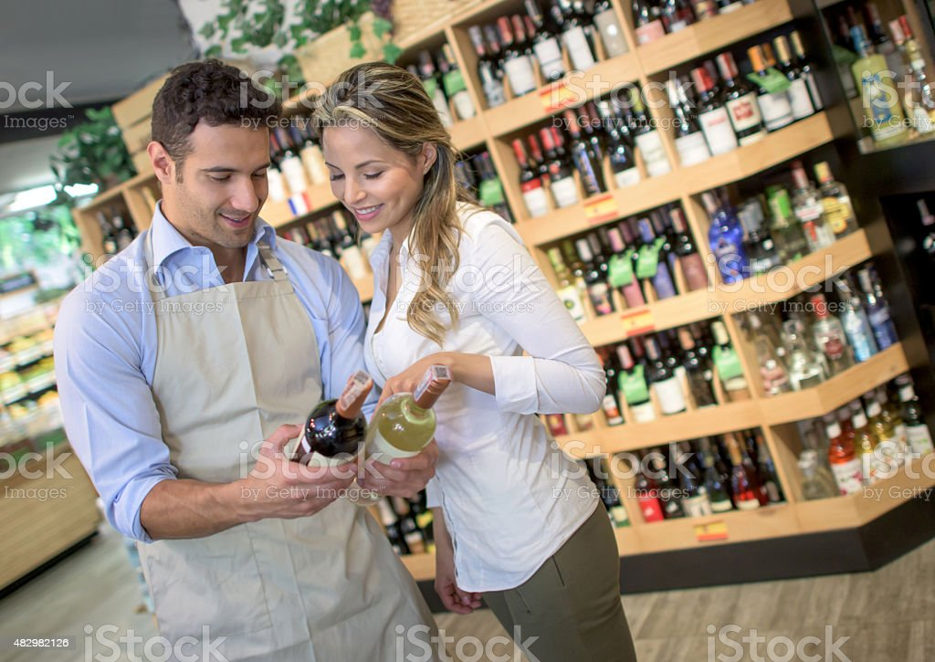 Sommelier helping woman buy a bottle of wine stock photo