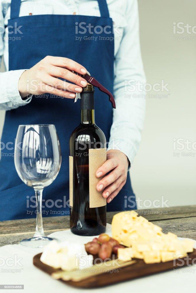 sommelier opening bottle of white wine stock photo