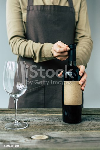Female Sommelier in apron opening the bottle of red wine