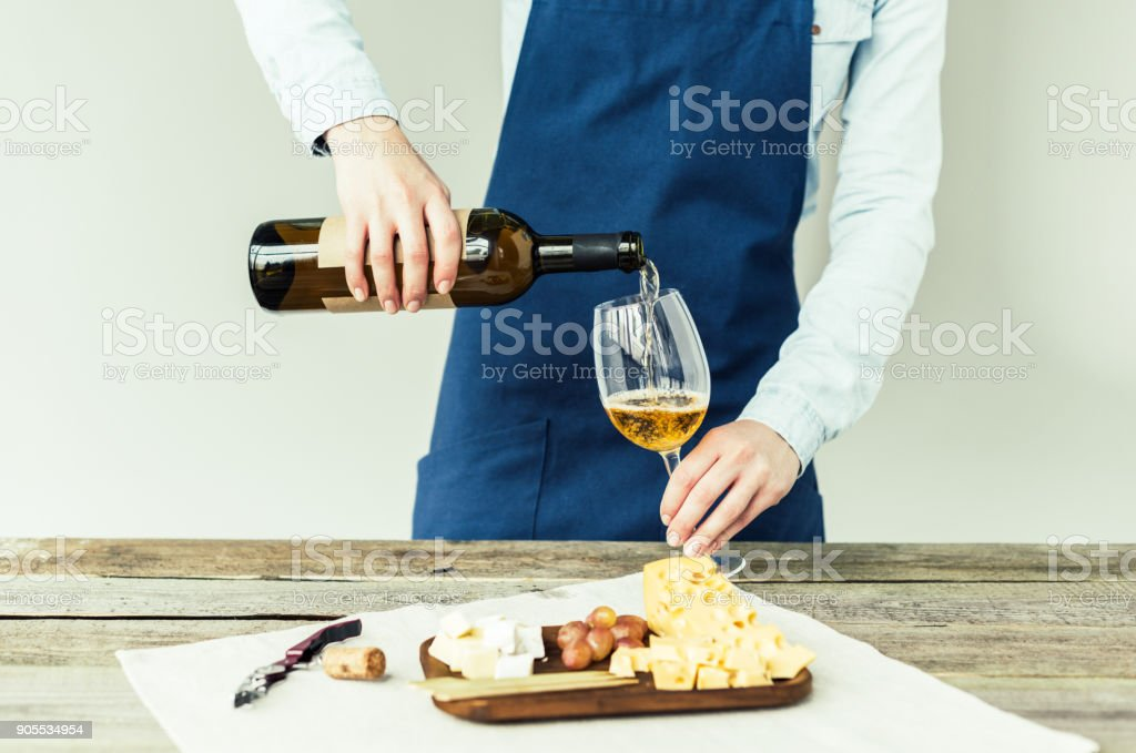 sommelier pouring white wine into glass stock photo