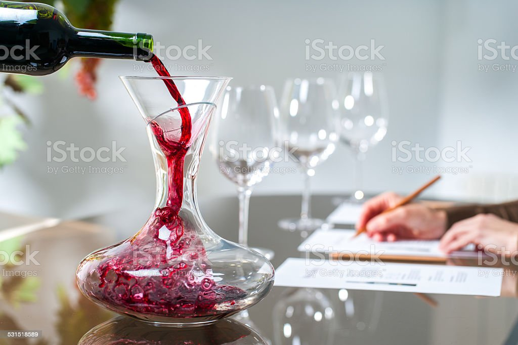 Sommelier pouring wine into decanter. stock photo