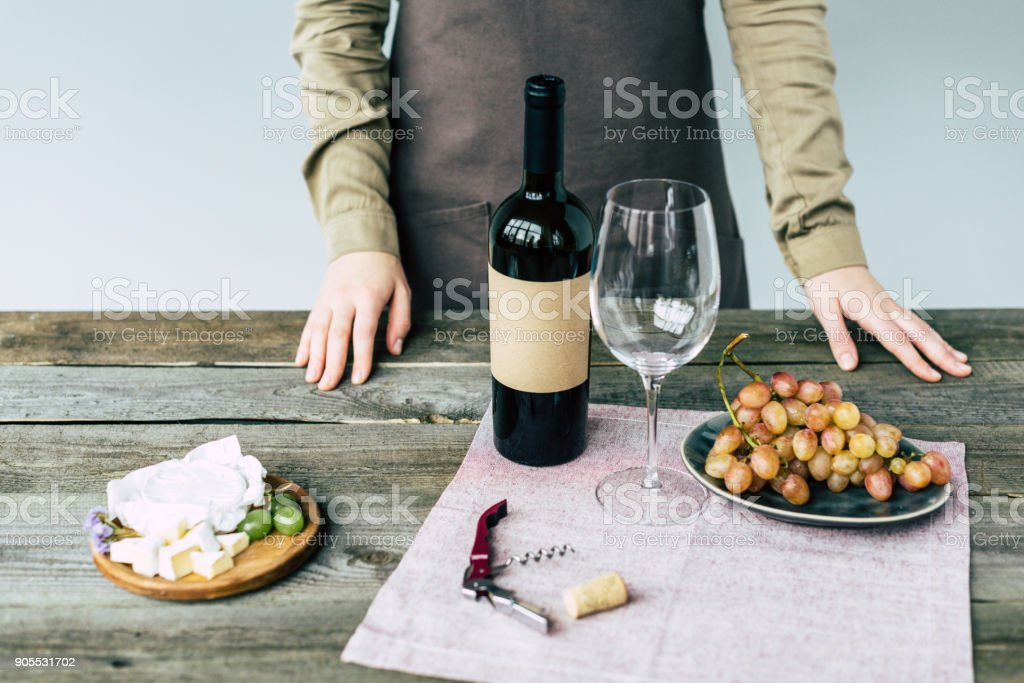 sommelier standing near table with wine stock photo