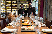 Team of sommeliers hosting a winetasting event at a cellar wearing facemasks during the COVID-19 pandemic