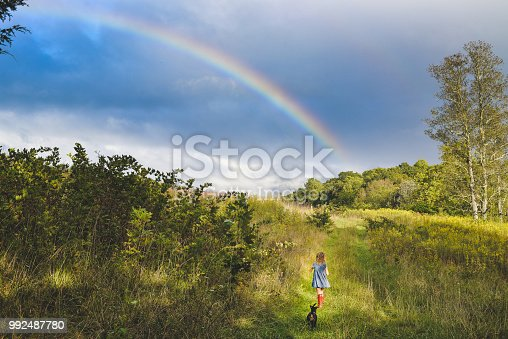 Over the rainbow... Adorable little girl in a blue dress and red boots in a vast nature field meadow area with a stunning rainbow in the sky. She is headed for adventure or maybe to find home?