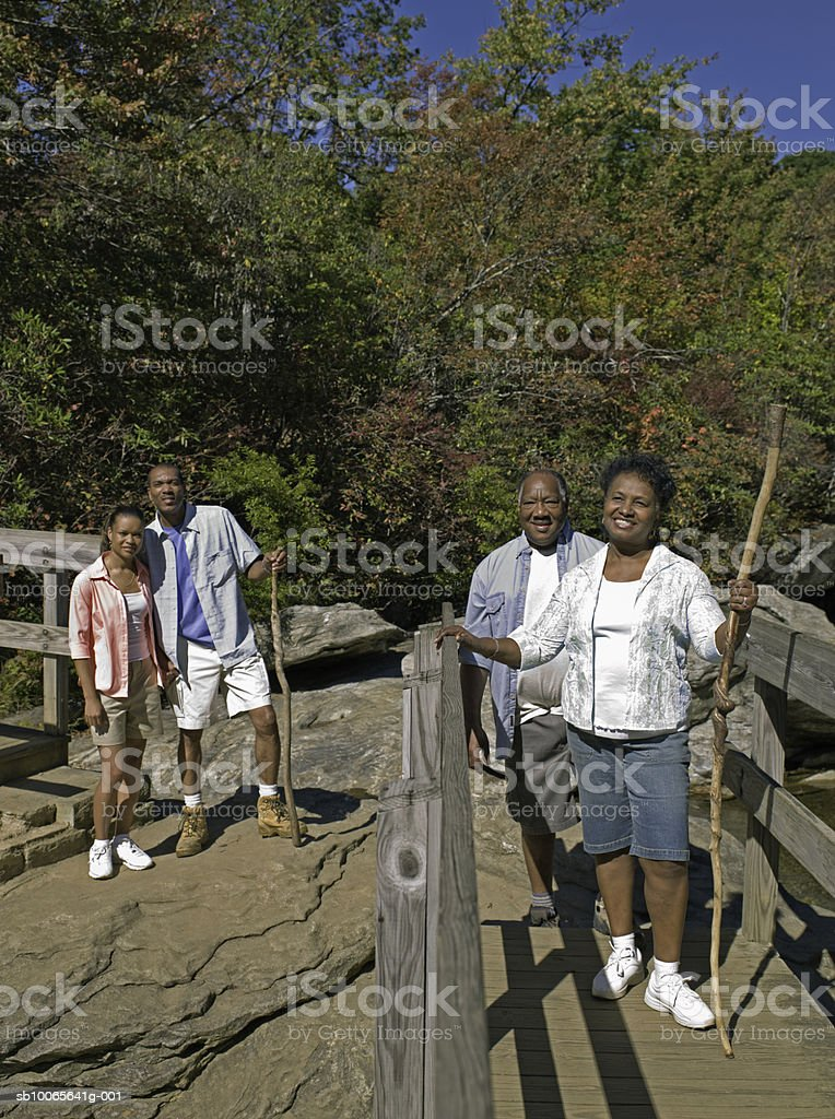 Son and daughter in law with mother and father hiking across bridge foto de stock libre de derechos