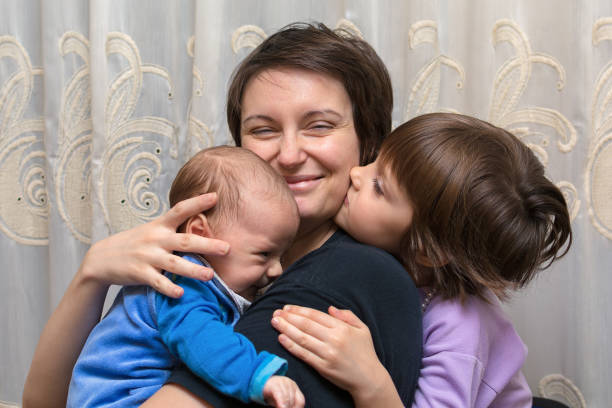 Sohn und Tochter küssen ihre Mutter – Foto