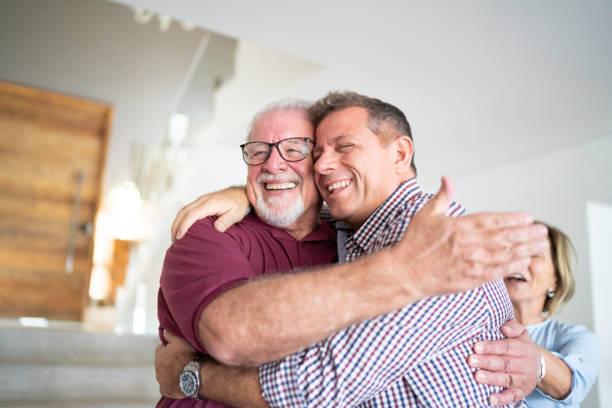 son and father embracing - filhos adultos imagens e fotografias de stock