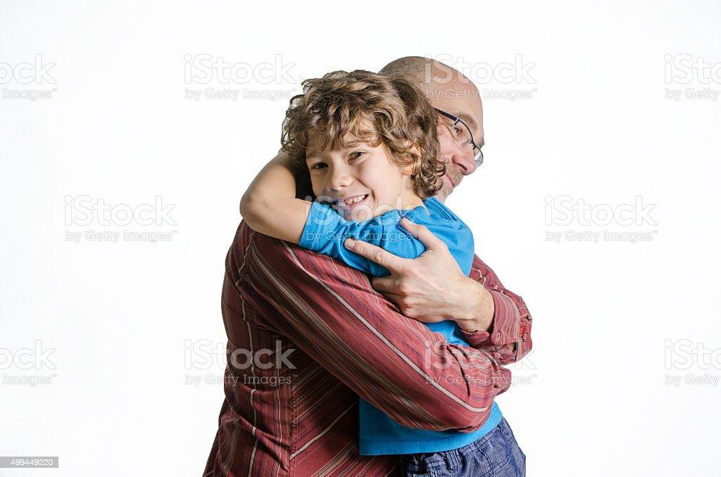 Son and father hug on white background studio stock photo