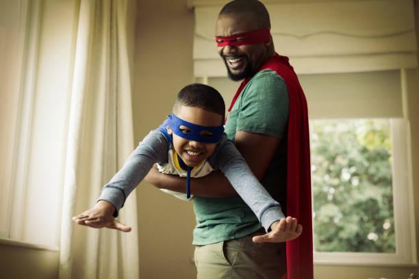 fils et père faisant semblant d'être un super-héros à la maison - père photos et images de collection