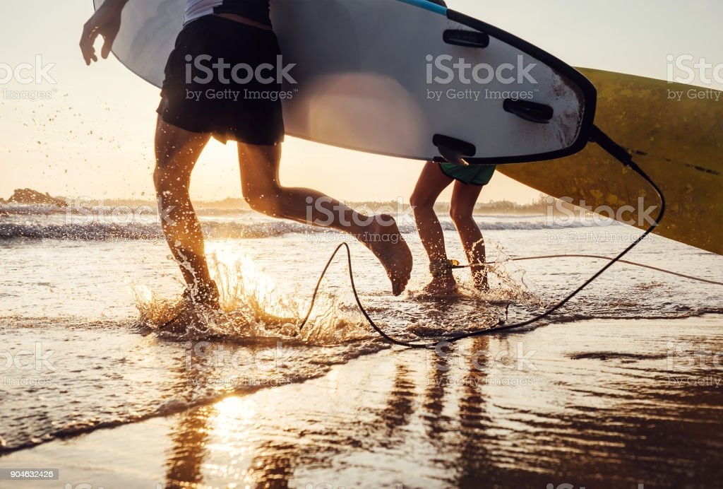Son and father surfers run in ocean waves with long boards. Close up splashes and legs image stock photo