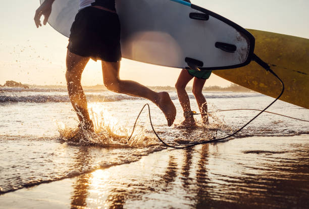 son and father surfers run in ocean waves with long boards. close up splashes and legs image - surf foto e immagini stock