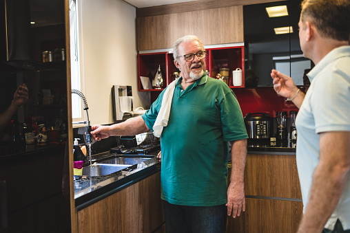 Son and father talk after cleaning kitchen sink