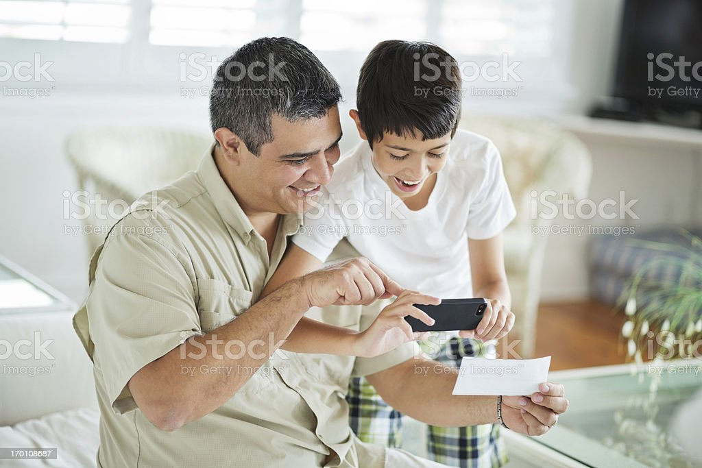 Son And Father Using Mobile Phone To Deposit Check stock photo