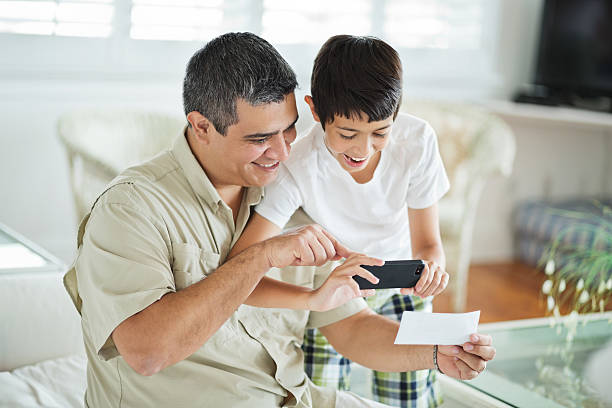 son and father using mobile phone to deposit check - deposit slip stock photos and pictures