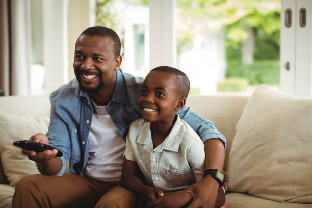 Son and father watching television stock photo