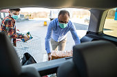 Son and father with surgical masks packing groceries from supermarket in car trunk at parking lot