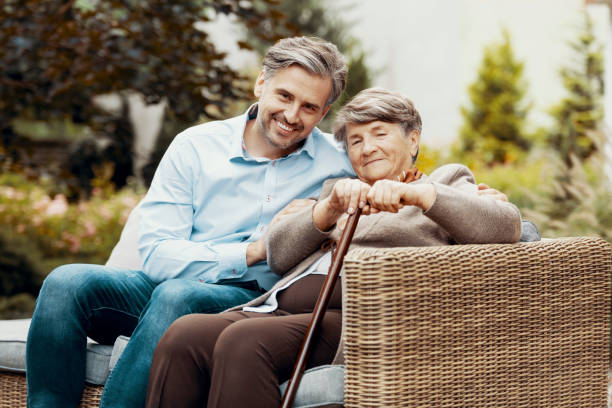Son and mother with a cane sitting on a wicker sofa in a garden Son and mother with a cane sitting on a wicker sofa in a garden wicker stock pictures, royalty-free photos & images