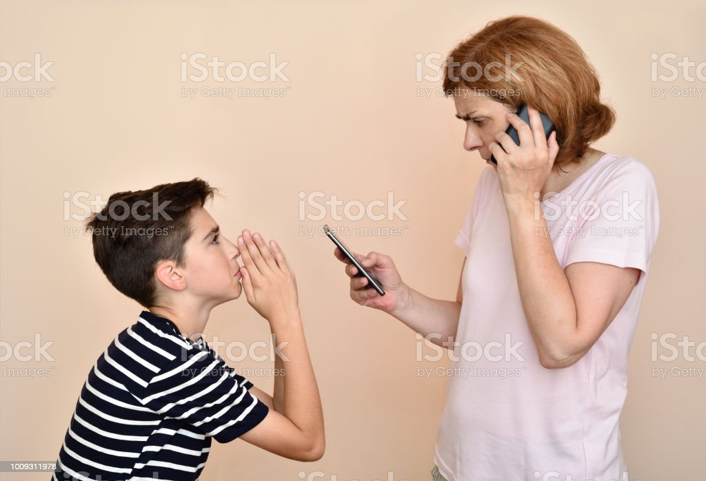 Son begging his angry and nervous mother for attention stock photo