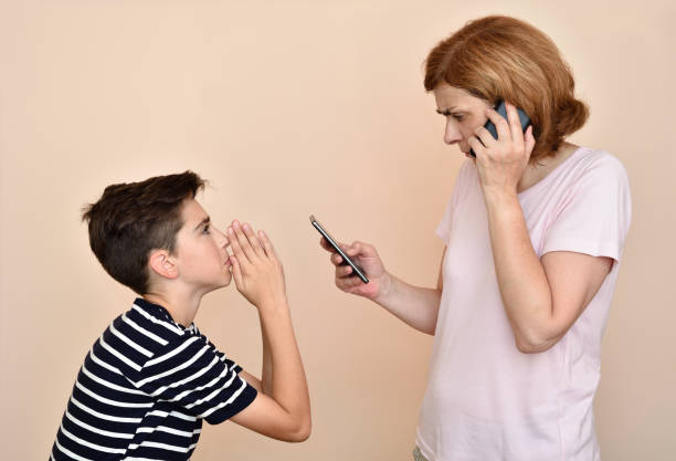 Son begging his angry and nervous mother for attention Son begging his angry and nervous mother for attention. She is using two smartphones at the same time and ignoring her son. Family and modern technology addiction concept. pleading stock pictures, royalty-free photos & images
